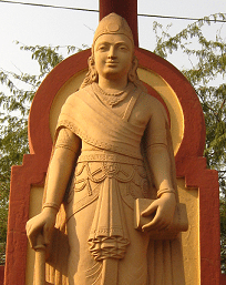 Chandragupta - Statue of a standing young man in red stone.